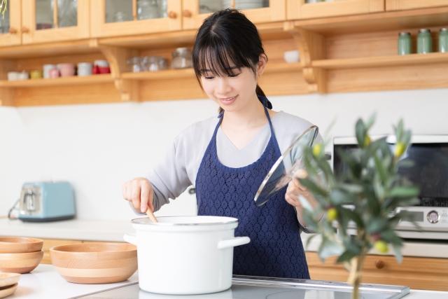 鍋で料理をする女性